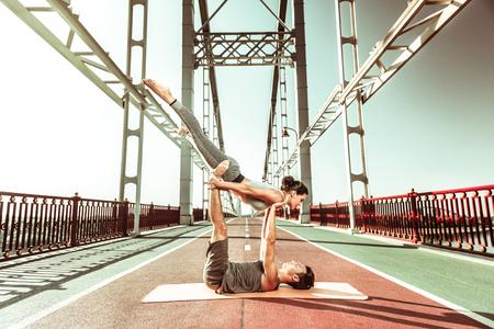 Morning yoga. Young couple enjoying the morning while practicing acroyoga outdoors on the bridge Stockfoto - 124983403