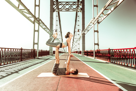 Developing arm balance. Strong Caucasian tanned dark-haired girl with her eyes closed doing a handstand outdoors in good weather Stockfoto - 124983407