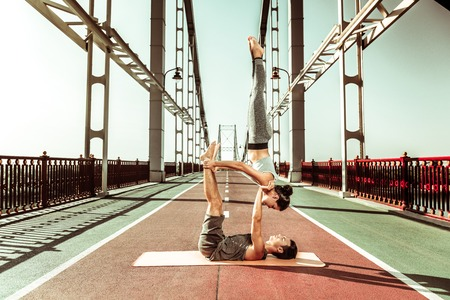 Candle stick asana. Sporty fit couple doing a shoulder stand candlestick acro yoga pose outdoors Stockfoto - 124983411