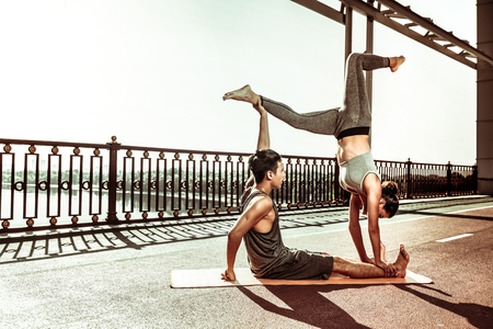 Sporty people. Side view of a healthy young couple in sportswear doing various acrobatic yoga poses in pair outdoors Stockfoto - 124983412