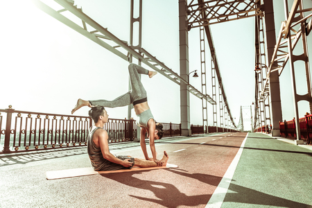 Acroyoga concept. Female yogi doing a handstand supported by her male partner sitting on an orange exercise mat