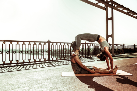Couple practicing asanas. Slim young woman standing in a wheel pose assisted by her partner sitting on the pedestrian bridge