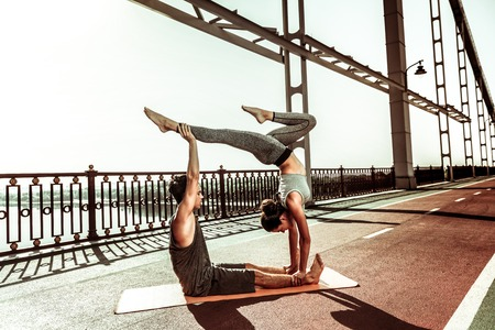 Acro moves. Strong young girl standing with her head downwards while doing a handstand on the bridge Stockfoto - 124983436
