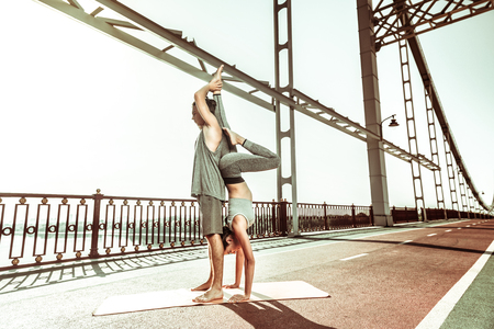 Active lifestyle. Slim young woman practicing a candle stick asana assisted by her yoga partner Stockfoto - 124983437