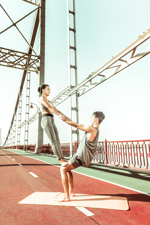 Thigh stand asana. Vertical shot of two young beautiful yogis doing a thigh stand acroyoga pose on the bridge Фото со стока