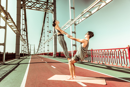 Sport in nature. Young Caucasian female and male practicing acrobatic yoga together on a mat outdoors