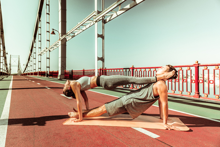 Harmony with nature. Couple of young yogis doing their stretching workout outdoors in fine summer weather Фото со стока