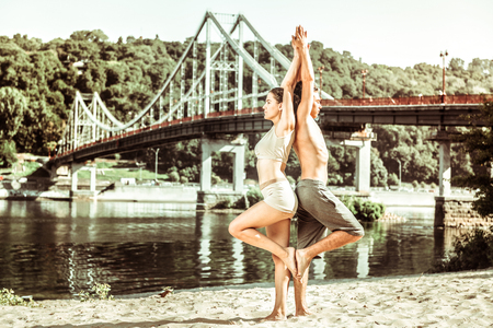 Healthy lifestyle. Young serious couple stretching while doing yoga exercises outside on a sunny morning
