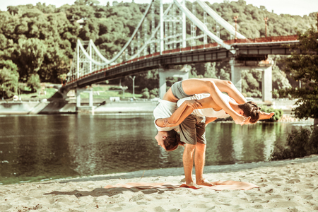 Coherent teamwork. Active sporty dark-haired girl and boy increasing their flexibility by performing acroyoga asanas outdoors