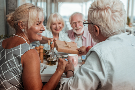 Happy together. Delighted mature people expressing positivity while spending time with family