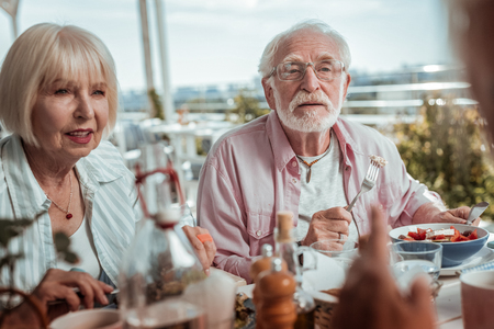 Enjoy your meal. Attentive bearded man sitting near his wife while eating salad