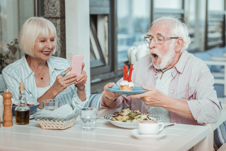 Funny moment. Emotional bearded man opening mouth while blowing candles on cake Stock Photo - 124983581