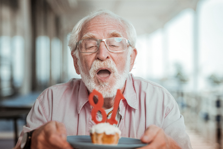 Join me. Delighted man holding plate with dessert while celebrating his birthday 스톡 콘텐츠