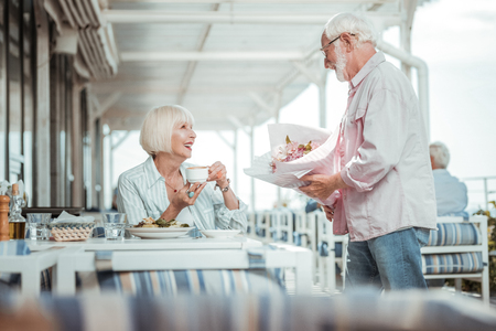 In love. Handsome pensioner holding bouquet in both hands while having date in cafe Stock Photo