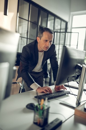 Overloaded businessman. Prosperous and successful businessman feeling overloaded in the office