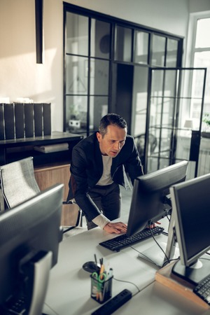 Checking e-mail. Mature dark-haired prosperous businessman checking his e-mail on computer