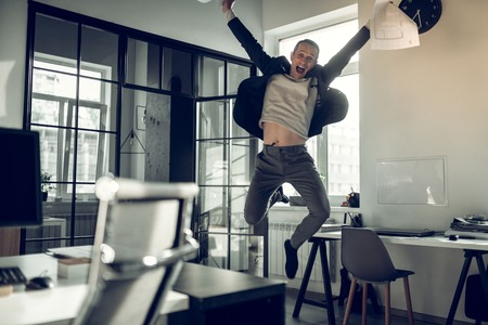 Businessman jumping high. Mature businessman jumping high after successful deal with business partner
