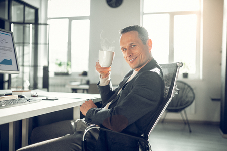 Mature man smiling. Handsome mature man smiling while drinking good coffee in the office after work