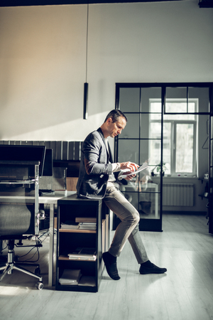 Working in office. Stylish mature man wearing dark suit working in the office and reading documents