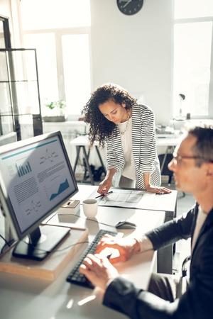 Standing near boss. Curly stylish secretary standing near her busy boss working on computer