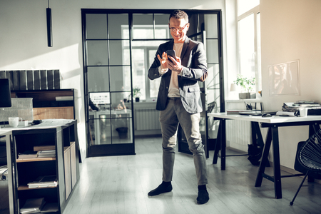 Standing in the office. Businessman standing in the office and using his smartphone having little break Banco de Imagens