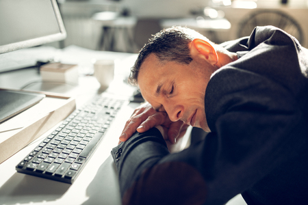 Falling asleep. Exhausted mature businessman falling asleep on working table feeling too tired