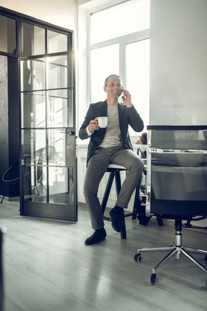Businessman smiling. Stylish mature businessman smiling while having phone call from friend Banco de Imagens