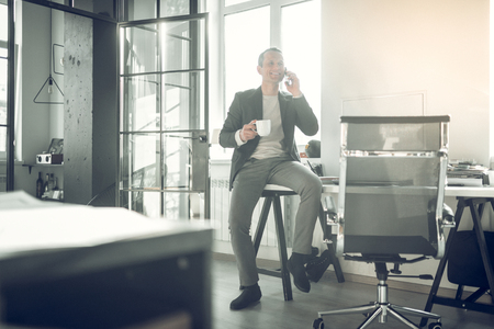 Sitting on table. Stylish businessman sitting on table and calling his business partner having little break Imagens