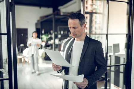 Reading some report. Mature serious businessman reading some report and documents standing in the office Imagens