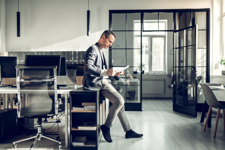 Prosperous businessman. Stylish prosperous businessman sitting in the office and reading documents Imagens