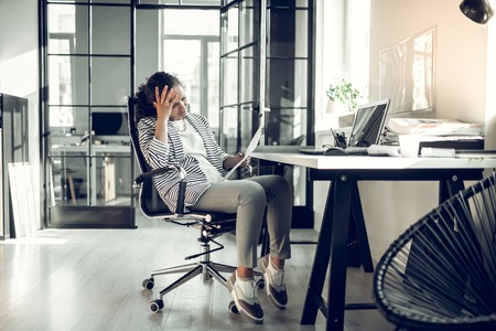 Having headache. Secretary wearing striped jacket having headache after difficult task from her boss Imagens