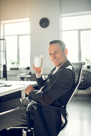 Cheerful businessman. Cheerful handsome businessman feeling satisfied after work while drinking coffee Stock Photo