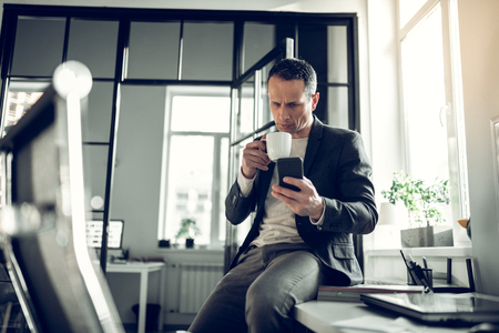 Reading message. Mature successful businessman having coffee break and reading message on phone Imagens