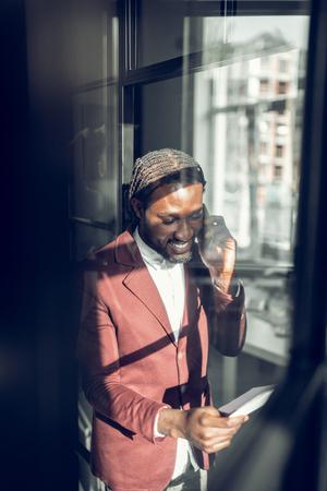 Receiving phone call. Bearded cheerful dark-skinned businessman receiving phone call from old friend