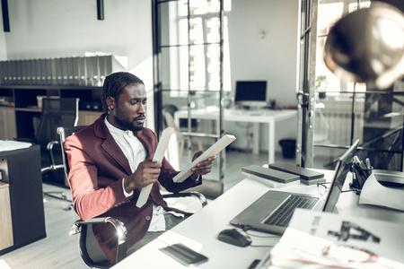 Dark-skinned designer. Bearded dark-skinned interior designer working on new project in the office