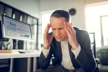 Suffering from headache. Dark-haired mature businessman feeling extremely awful suffering from headache