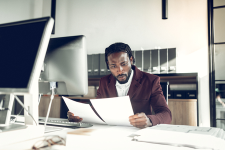 African-American businessman. Stylish African-American businessman reading the financial reports in the office
