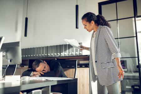 Assistant sleeping. Stylish businesswoman feeling furious looking at her assistant sleeping