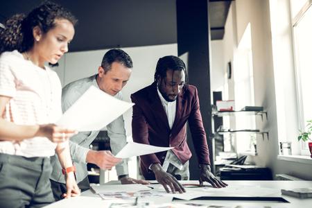 Designers having brainstorming. Team of interior designers having brainstorming about new project in office