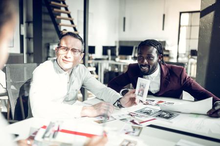 Owning fashion magazine. Businessman wearing glasses owning fashion magazine talking to his employees Фото со стока