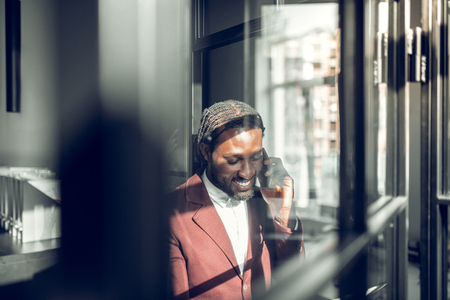 Speaking on phone. Dark-skinned handsome businessman speaking on the phone with his old friend