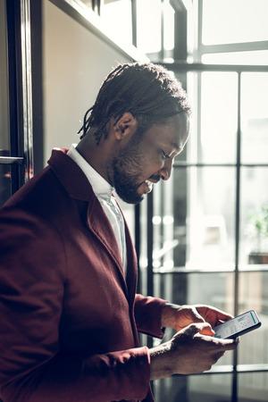 Using smartphone. African-American businessman using his smartphone having little break