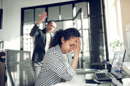 Employee having headache. Curly dark-haired employee having headache listening to angry boss Imagens