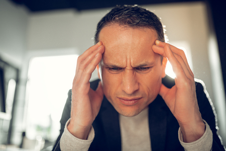 Man with headache. Close up of mature businessman suffering from headache and high pressure