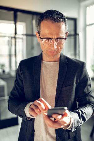 Reading message. Mature good-looking businessman wearing dark jacket reading message on phone Banco de Imagens