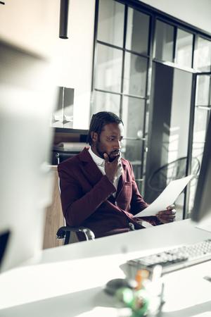 Bearded businessman. Bearded businessman wearing stylish jacket feeling thoughtful while reading documents 版權商用圖片