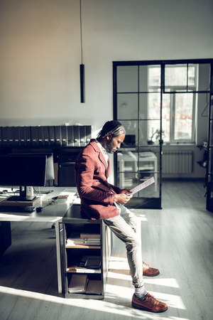 Near working table. Stylish dark-skinned businessman standing near working table and reading documents