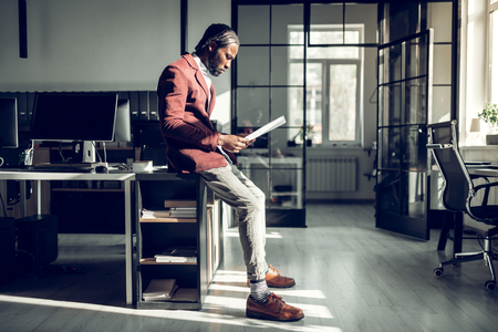 In stylish trousers. Dark-skinned businessman wearing stylish trousers reading important financial reports