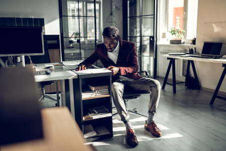 Busy businessman. Businessman wearing striped socks and stylish trousers feeling busy while working