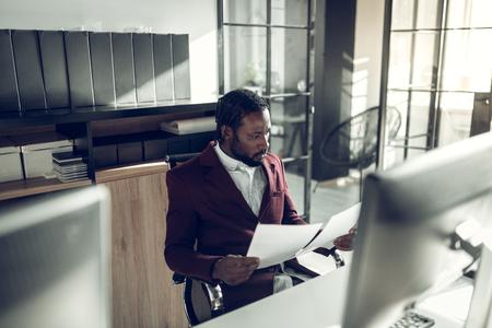 Dark-skinned businessman. Bearded dark-skinned businessman feeling involved in reading documents in office